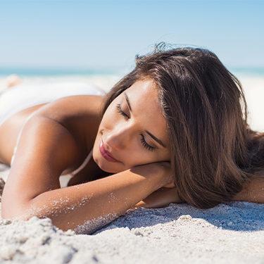 woman laying down at beach